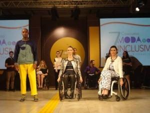 Foto do desfile com roupas inclusivas; três modelos estão em uma passarela. O primeiro modelo é um homem negro e jovem, à esquerda; as duas outras modelos, mulheres brancas e jovens, estão em cadeira de rodas