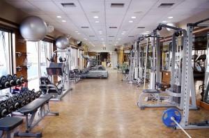 Foto de uma academia de ginástica vazia. Há vários aparelhos de musculação, com halteres e pesos de diferentes formatos e tamanhos.
