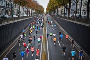 Foto aérea de uma grande avenida asfaltada; pessoas de diversas idades correm por esta avenida, em uma maratona de atletismo