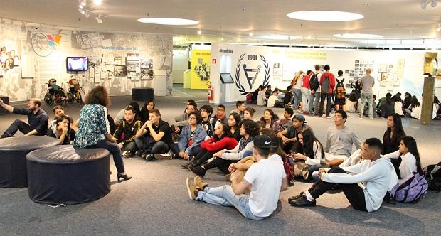 Foto de uma das salas do Memorial da Inclusão; a sala é ampla, com colunas e obras penduradas nas paredes; um grupo de pessoas de diversas idades está sentada no chão, enquanto uma mulher, sentada em um puff, conversa com eles