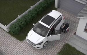 Imagem aérea de um veiculo branco estacionado, com as portas e o porta-malas abertos. Há uma cadeira de rodas próxima ao veículo