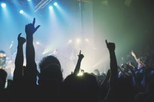 Foto de um show com destaque da multidão com as mãos para cima assistindo banda tocar em um palco.