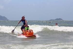 Foto em uma praia em um dia ensolarado. Mara Gabrilli está em uma prancha de surf adaptada para ela. Na mesma prancha está um homem que oferece apoio e segura um remo.