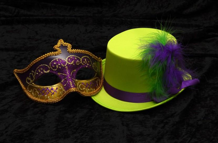 Foto de uma máscara veneziana e um chapéu verde limão com plumas nas cores verde e lilás em um fundo preto.