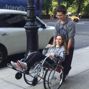 Foto de moça cadeirante levada por um jovem. Ele a inclina e os dois sorriem.