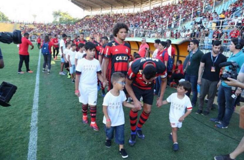 Foto com jogadores do Flamengo entrando em campo em fila. Eles estão de mãos dadas com crianças cegas vestidas com um uniforme branco, onde se lê na camiseta: Paixão Cega.