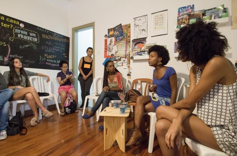 Em uma sala fechada, mulheres estão sentadas em cadeiras dispostas em círculo. Três delas olham em direção a uma delas. Há uma parede com cartazes e quadros e outra com palavras escritas em giz.
