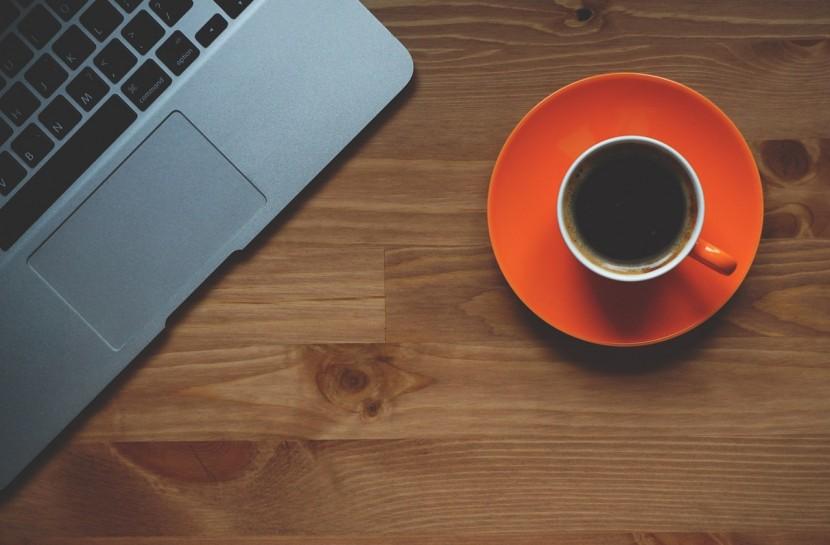 Foto que mostra parte do teclado de um laptop com uma xícara de café ao lado.