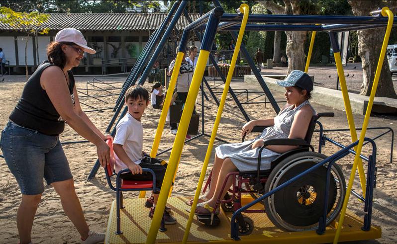 Foto de duas crianças sentadas em um balanço de metal. Uma mulher segura uma das cadeiras. A criança que está no lado direito da imagem está em uma cadeira de rodas.