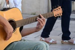 Foto de um homem sentado com um violão no colo. Ele está de perfil, segurando o braço do violão, em primeiro plano.