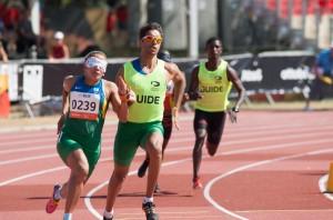 Foto da atleta Terezinha Guilhermina. Ela tem os olhos vendados e corre em uma pista de atletismo ao lado de seu guia. Ela está à frente de outro atleta e seu guia, que estão mais ao fundo.