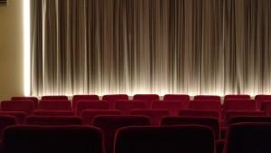 Foto de uma sala de cinema vazia. Ao fundo, uma cortina branca. As cadeiras são vermelhas.