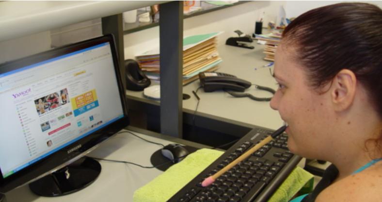 Foto da Joyce, de perfil, usando uma paleta de boca na frente de um computador.