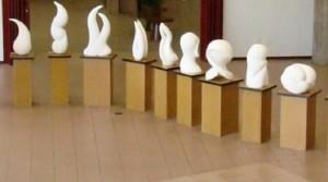 Foto traz nove esculturas da exposição Movimento em Branco. Apoiadas sobre totens, elas são pequenas, brancas e possuem formas abstratas.