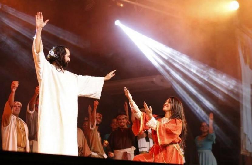 Cena do musical traz um ator caracterizado como Jesus. Ele tem um dos braços erguidos e abençoa, com o outro, uma mulher que está agachada e sorri para ele com os mãos em sinal de pedido.