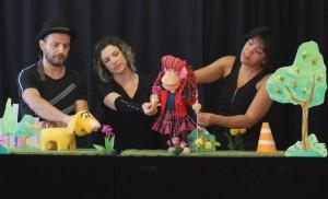 Foto do espetáculo. Em um palco, três pessoas manipulam fantoches de uma menina e um cachorro