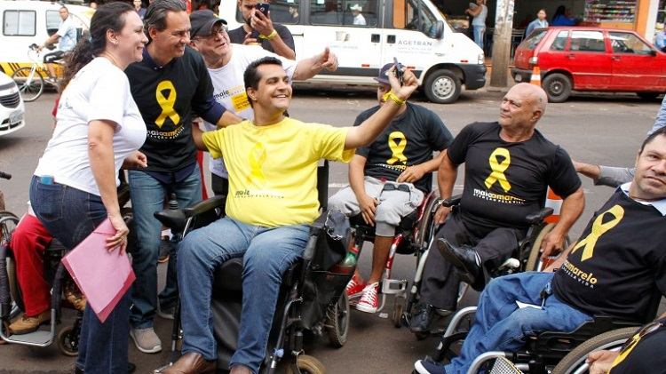 Foto de um estacionamento. Em destaque, cadeirantes de diversas idades ocupam vagas para carros. Eles sorriem e gesticulam