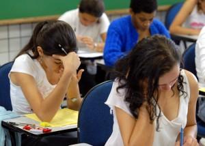 Foto de uma sala de aula, com diversos jovens sentados em carteiras, durante aplicação da prova do Enem