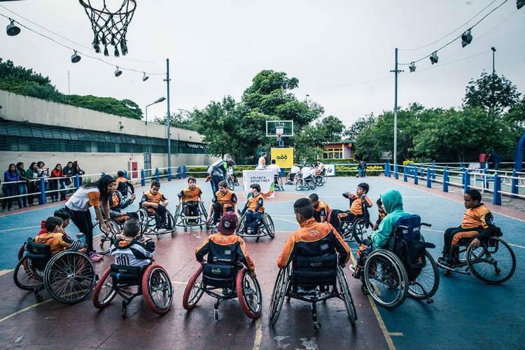 Foto do time de basquete de cadeira de rodas, na quadra. Dispostos em um círculo, os atletas olham para uma mulher que está de pé. Mais ao fundo, outro time está disposto em um círculo.