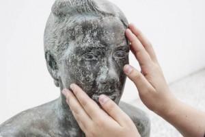 Foto da escultura de um busto, em pedra. Duas mãos a tateiam