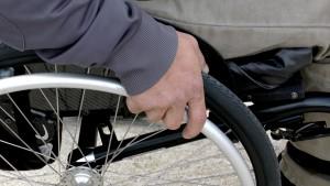 Foto de um homem sentado em uma cadeira de rodas. Uma das mãos dele segura aro de impulsão da cadeira de rodas.