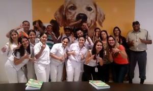 #PraCegoVer Foto de 17 pessoas, em uma sala da empresa Mars. Elas sorriem enquanto fazem um sinal em Libras com as mãos