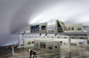 Foto em plano aberto da exposição mostrando dois andares da Oca. No chão, há diversas esculturas e, nas paredes, quadros de tamanhos diversos