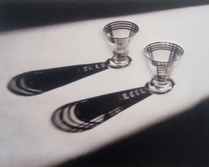 Foto de obra tátil que representa uma fotografia com dois copos em cima de uma mesa e suas sombras