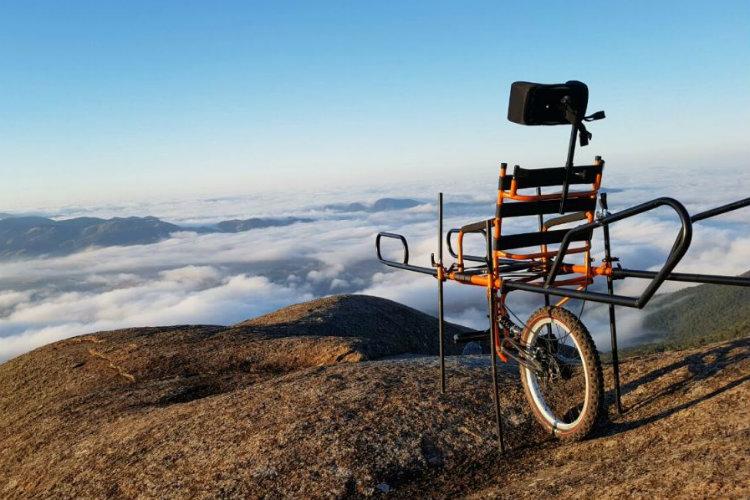 Foto em plano aberto de cadeira de rodas adaptada, com apenas uma roda e barras para que ela possa ser carregada, no topo de uma montanha