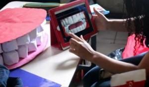 Foto de uma sala de aula. Sobre uma mesa escolar há o protótipo de arcada dentária humana em tamanho grande. À frente, mãos seguram um tablet que mostra esses dentes em uma animação 2D