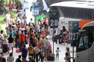 Foto em plano geral de um terminal rodoviário; há um ônibus estacionado e muitas pessoas embarcando na plataforma