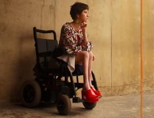 Foto de uma jovem modelo cadeirante posando em uma galpão antigo, com um vestido. Ela olha na direção direita com semblante contemplativo