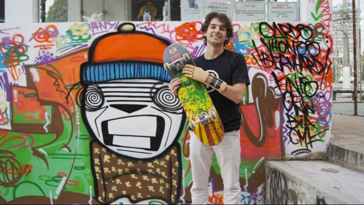 Foto de um jovem rapaz em frente a um muro grafitado. Ele usa uma prótese na mão esquerda e segura um skate