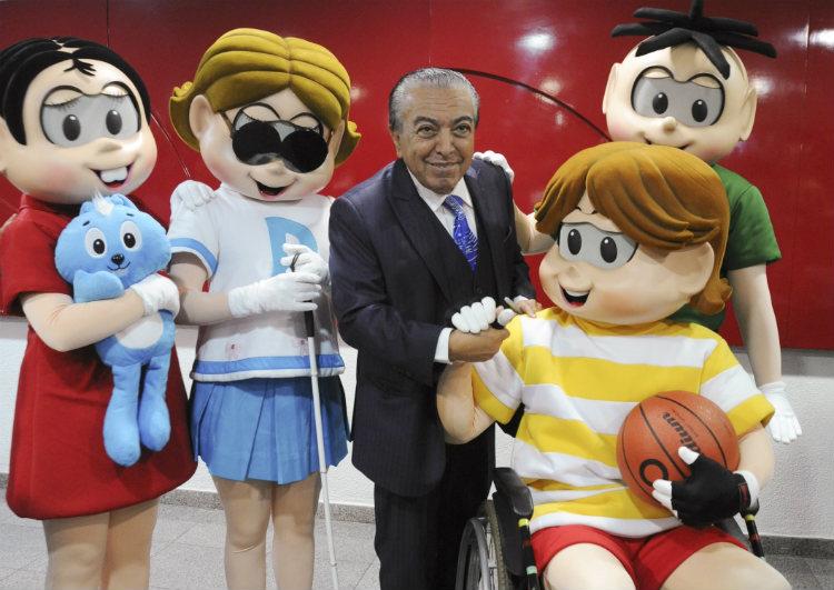 Foto do cartunista Maurício de Sousa posando ao lado de seus personagens. Da esquerda para a direita: Mônica, Dorinha, que tem deficiência visual, Maurício, Luca, que é cadeirante, e Cebolinha