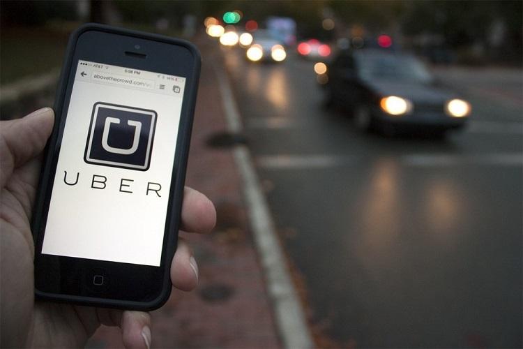 Foto de uma mão, em primeiro plano, segurando um smartphone com o logo do Uber na tela. Ao fundo, há uma avenida movimentada