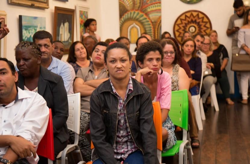 Foto de um espaço amplo, fechado, com uma fila de pessoas de diversas idades em destaque