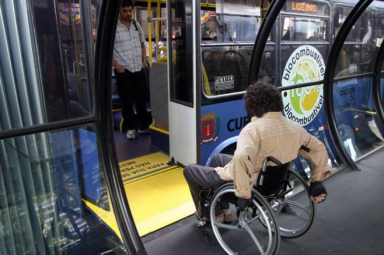 Foto de um cadeirante embarcando em um ônibus por um elevador acessível