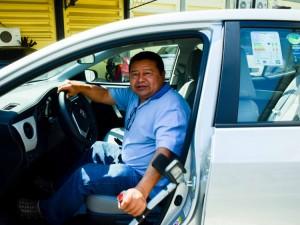 Foto de um senhor com muletas, saindo de um carro, do lado do motorista