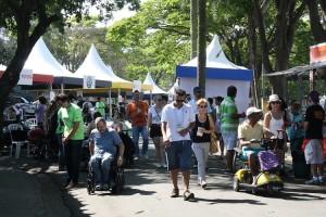Foto de um espaço aberto, com tendas montades e pessoas de diversas idades circulando, entre elas, cadeirantes