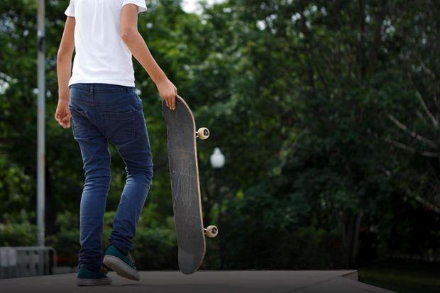 Foto de um jovem segurando um skate em um espaço aberto