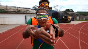 Foto em close da atleta Terezinha Guilhermina e seu técnico, Guilherme, em uma pista de atletismo. Ela tem os olhos vendados, e alonga os braços na direção da câmera. Ele está atrás dela, auxiliando com seus braços.