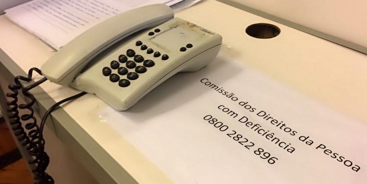 Foto de uma mesa com um telefone de fio apoiado. Ao lado, há um cartaz colado no tampo da mesa, com os dizeres: Comissão dos Direitos da Pessoa com Deficiência 0800 2822 896