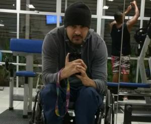 Foto de um homem moreno cadeirante, de 29 anos. Ele é malhado, usa touca e cavanhaque e faz uma selfie na frente do espelho, com o celular na mão