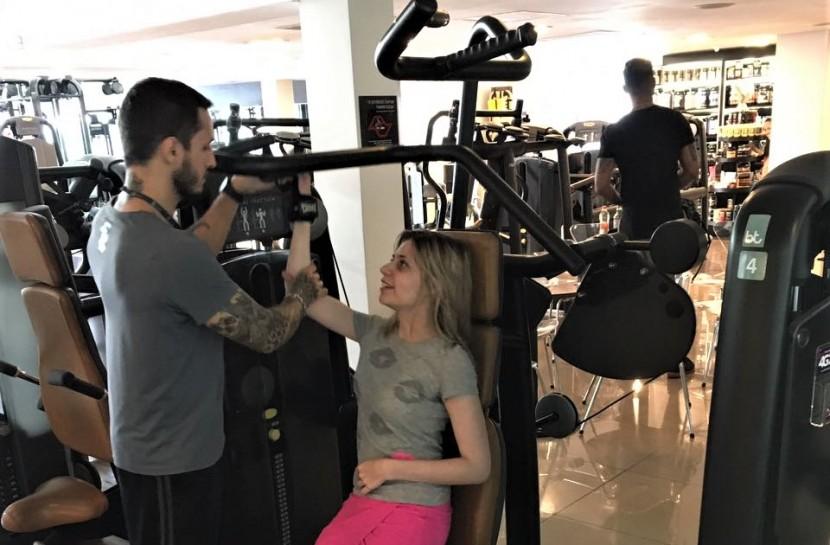 Foto da Nathalia na academia. Ela está sentada em um aparelho de musculação enquanto um homem segura seu braço direito no equipamento.