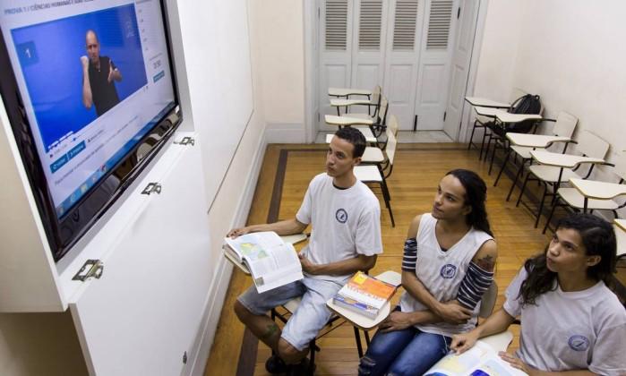 Foto de uma sala de aula, com três alunos, um garoto e duas garotas, de aproximadamente 16 anos. Eles olham para uma televisão. Nela, é mostrado um vídeo com um professor fazendo um sinal em libras com as mãos
