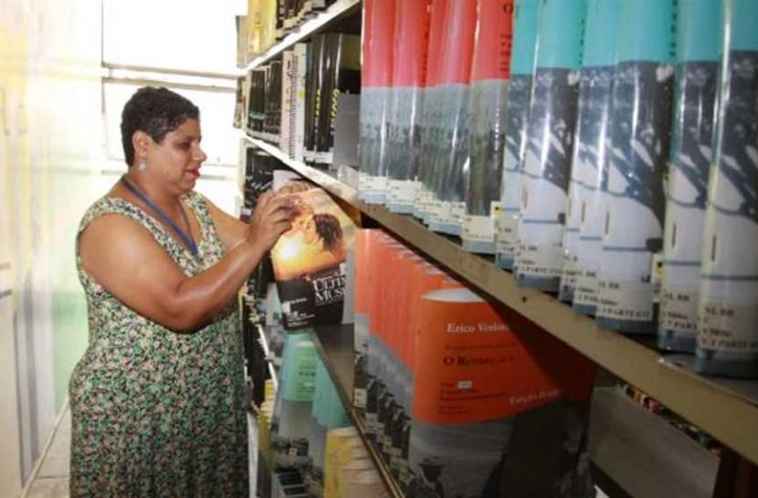 Foto de uma mulher com deficiência visual tatando livros em uma longa estante. Ela é negra, tem cabelos curtos e usa um longo vestido estampado.