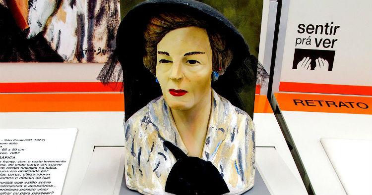 Foto do busto de uma mulher de meia idade. Ela tem cabelos castanhos curtos, usa chapéu preto, brincos azuis e uma blusa branca com manchas em diversos tons de azul e bege