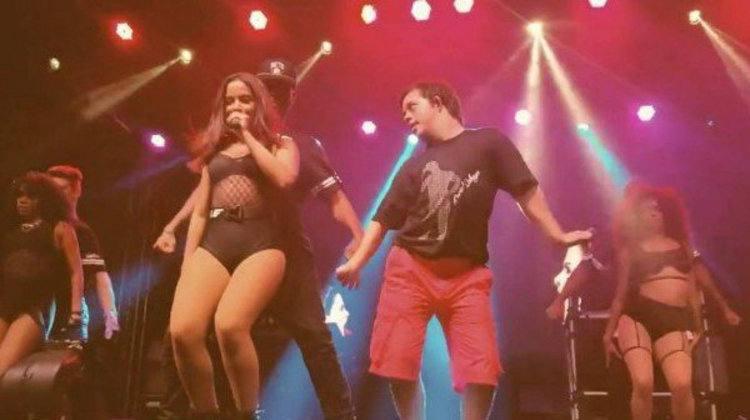 Anitta no palco com seus dançarinos - um deles com síndrome de Down