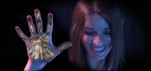 Foto de uma jovem mulher de olhos fechados, sorrindo. Sua mãe direita erguida está erguida e exibe projeções de fogos de artifício saindo da palma