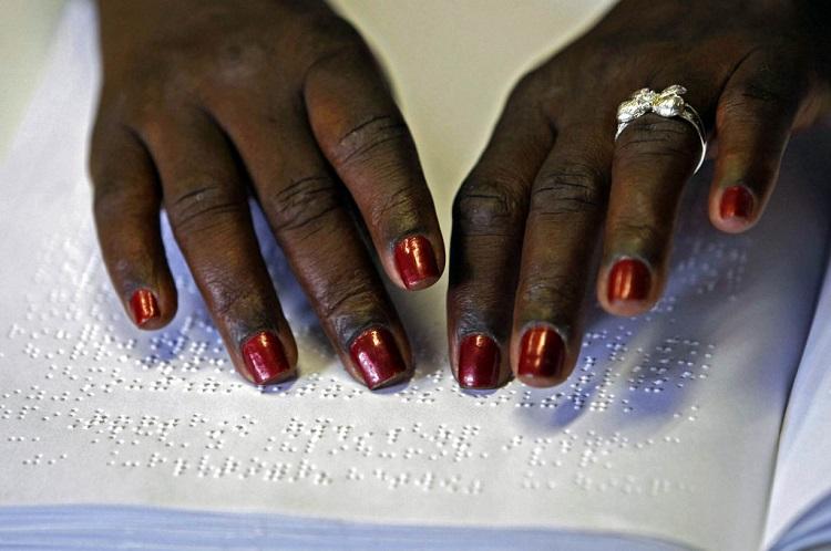 Mãos idosas e negras leem um texto em braile